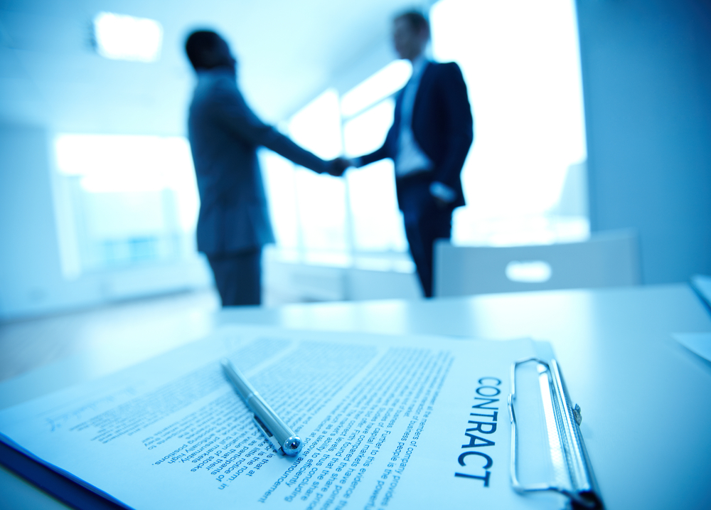 Handshake behind contract on table